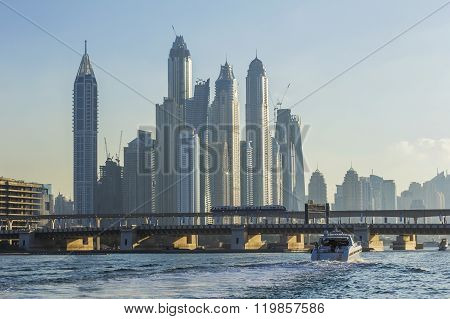 landscape motor boat passes under the bridge near skyscrapers Dubai