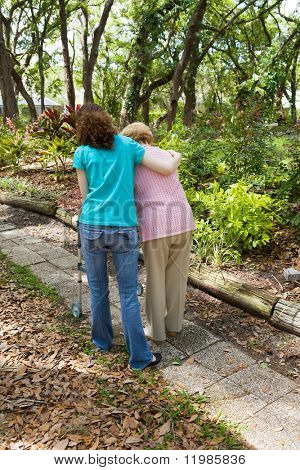 Teen girl helping senior woman walk through the park.  Vertical view with room for text.
