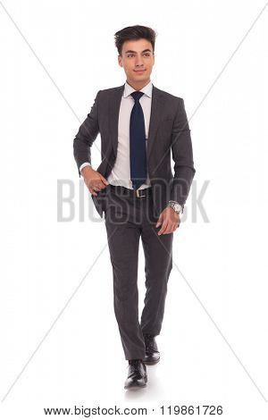 full body picture of a young business man walking and looking away from the camera on white studio background