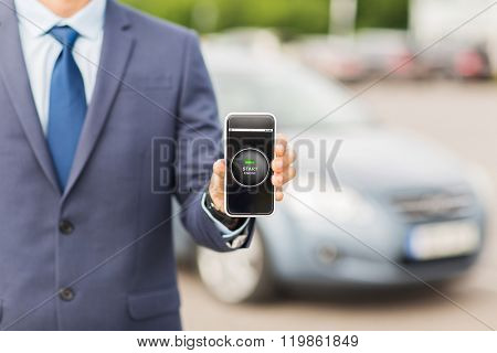 transport, business trip, technology and people concept - close up of man showing smartphone with ignition starter remote control application on screen on car parking poster