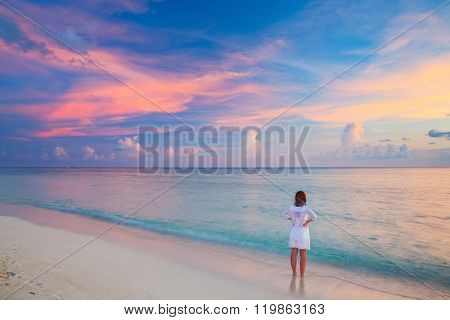 Young woman looking at sunset over ocean