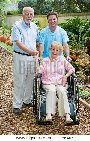 Disabled senior woman and her husband with a male nurse on the grounds of an assisted living facility.  Focus on the woman.