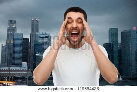 emotions, stress, urbanization, madness and people concept - crazy shouting man in t-shirt over evening singapore city background