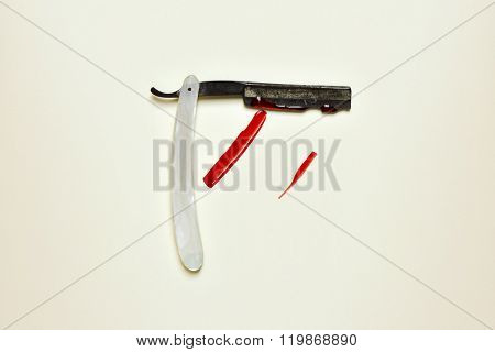 an old and rusty straight razor full of blood on an off-white background