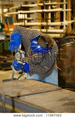 Welder using a grinder to smooth a piece of metal.  Authentic and accurate content depiction in compliance with industry code and safety standards.