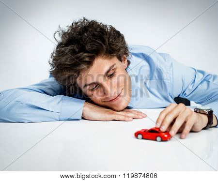 Young Adult Male Plays With Red Toy Car And Having Fun