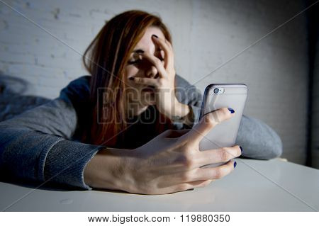 young sad vulnerable girl using mobile phone scared and desperate suffering online abuse cyberbullying being stalked and harassed in teenager cyber bullying concept