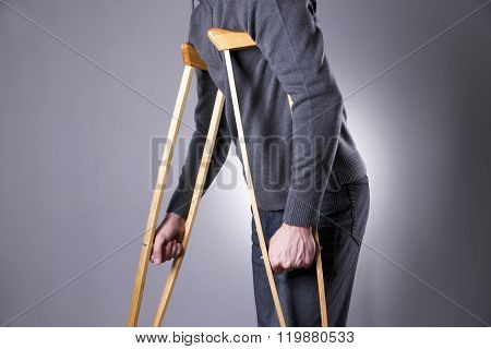 Man On Crutches On A Gray Background