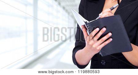 Woman writing in a diary book.