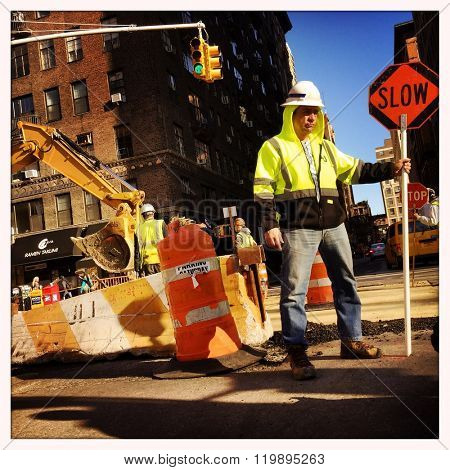 NEW YORK - 28FEB16: An unidentified construction worker holds a Slow sign to control traffic on corner of Waverly St and University Pl on February 28, 2016 in NYC.
