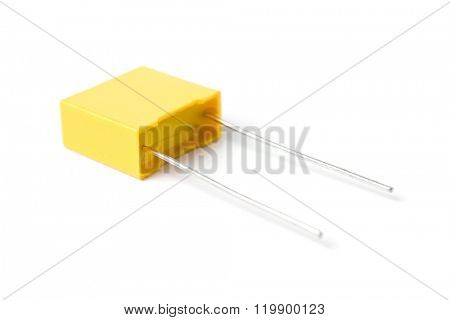 Yellow plastic-film capacitor isolated on white background.
