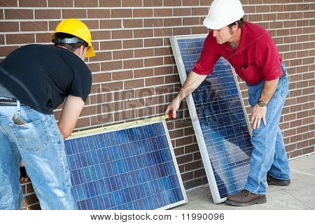 Electricians measuring solar panels they are about to install.