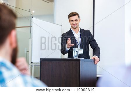 Smiling handsome businessman standing at tribune in conference hall and pointing in audience