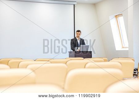 Thoughtful businessman writing speech on laptop in empty conference hall