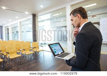 Pensive businessman looking on financial report on the screen of laptop standing in empty conference hall