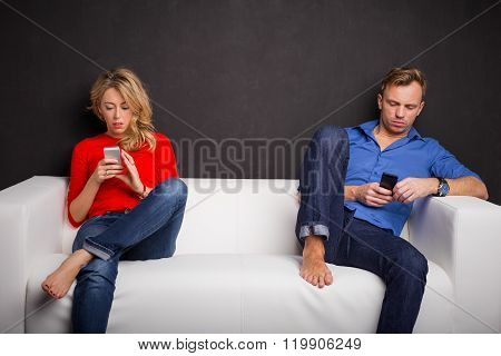 Couple sitting on couch with their phones in their hand