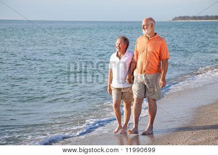Happy senior couple enjoys a romantic stroll on the beach.