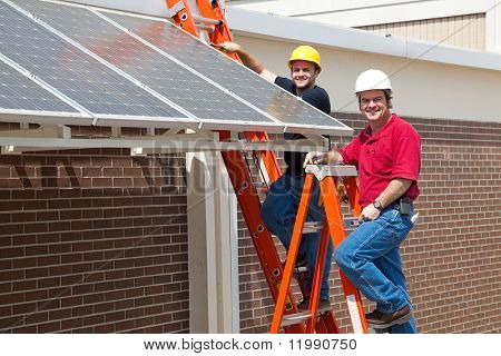Happy electricians employed to install energy efficient solar panels in the new green economy.