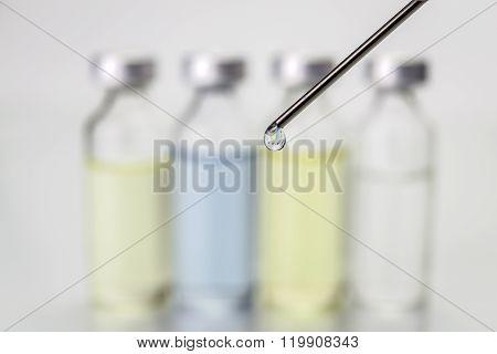Needle Of Syringe With Ampules On White Blurred Background