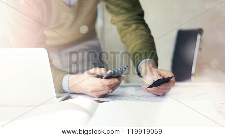 Business concept. Businessman holding hand businesscard and making photo smartphone. Architectural p