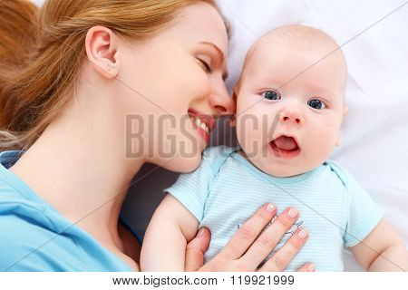 Happy Family Mother Kisses And Hugs Her Baby