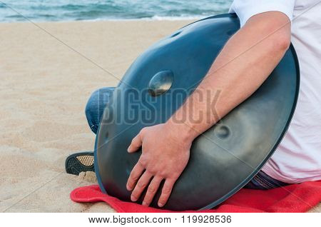 Relax music background. Hands percussion. Musician sit on sand and play the Hang or handpan. The han