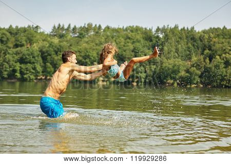 Father throws daughter in the water at the lake in summer