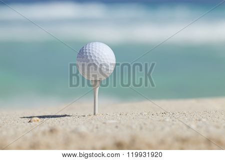 Golf Ball On Tee In Sand Beach With Ocean Waves Behind