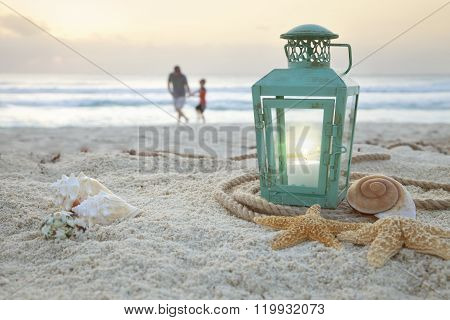 Lantern With Shells On Beach And Soft Focus Father And Son Collecting Shells At Sunrise