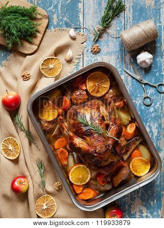 Barbecued chicken with various vegetables and garlic in baking dish.