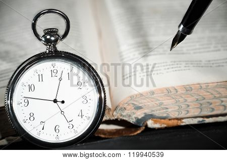 Pocket Watch On Book Over Black