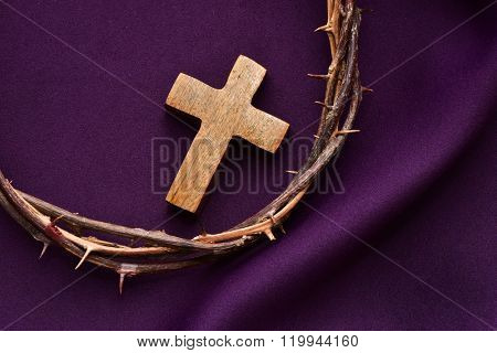 high-angle shot of a wooden christian cross and the crown of thorns of Jesus Christ on a purple drapery
