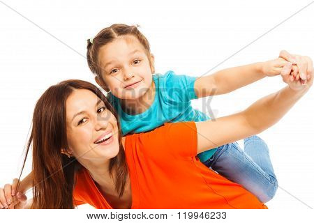 Smiling mother carrying her funny daughter pick aback like plane