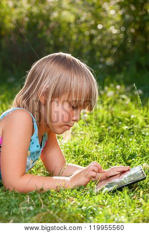 Little girl usng a touch pad in a summer garden