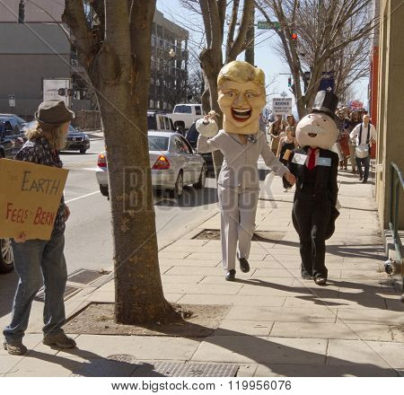 Asheville, North Carolina, USA - February 28, 2016: Humorous effigies of Hillary Clinton and Mr. Monopoly hold hands and carry bags of money as they skip down the street followed by marching Bernie Sanders supporters