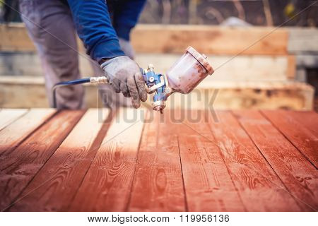 Industrial Handyman, Construction Worker Painting With Spray Gun On Site