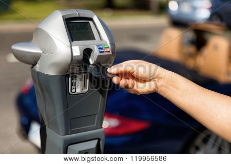 Hand Putting Credit Card Into Parking Meter With Convertible Car In Background