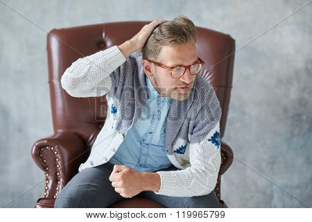 Portrait of a stylish intelligent man with glasses stares into the camera, good view, small unshaven