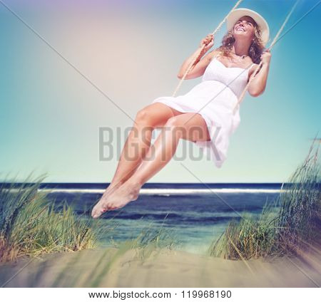 Beautiful Cheerful Woman Swinging by the Beach Concept