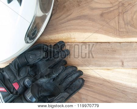 Black Gloves Motorcycle And White Helmet On Wood Table