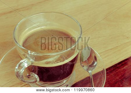 Black expresso coffee in small glass cup on wooden table with teaspoon vintage retro style.