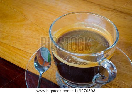 Black expresso coffee in small glass cup on wooden table with teaspoon