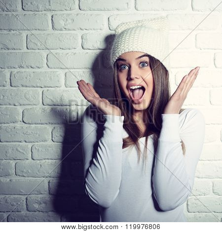 Portrait of young attractive cheerful hipster girl making funny faces, studio shot over white bricks background. Happiness, surprise, wonder, astonishment. Image toned.