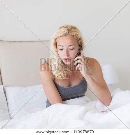 Woman talking by phone on bed in morning.