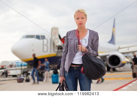Woman disembarking airplain.