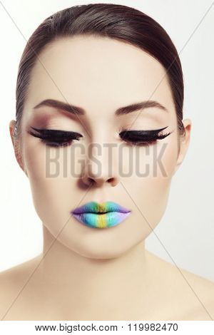 Vintage style portrait of young beautiful woman with winged eyes make-up and fancy rainbow ombre lips