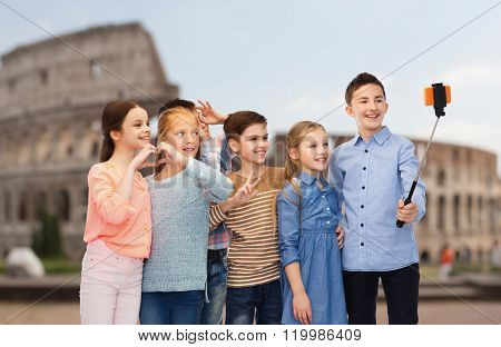 childhood, travel, tourism, technology and people concept - happy children talking picture by smartphone on selfie stick over coliseum in rome