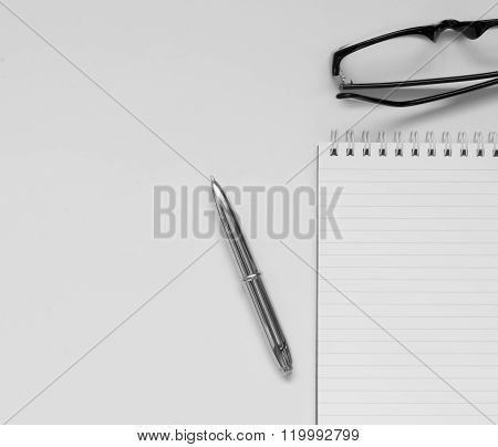 Glasses and notepad with pen. Isolated on white.