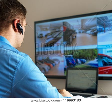 Security guard monitoring video in security room.