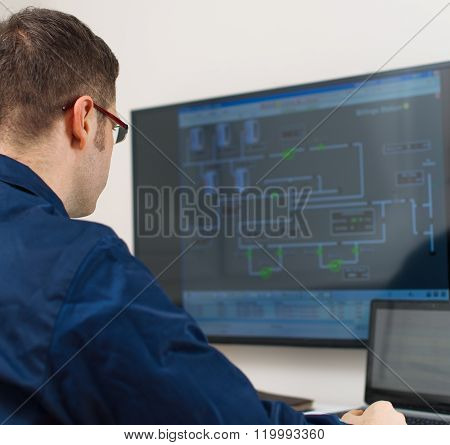 Male worker in glasses in thermal plant's control room.